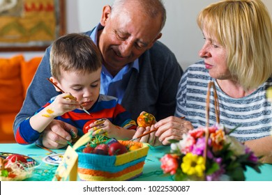 Grandparents with grandson paint eggs for Easter.