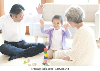 Grandparents and grandson play with blocks