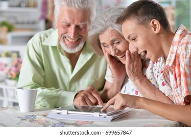 grandparents with grandson using laptop