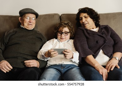 Grandparents and grandson using mobile at home.