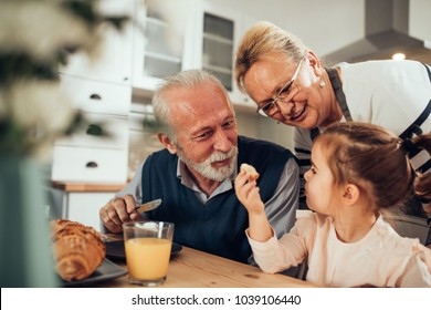 Grandparents having breakfast with their granddaughter