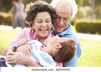 Grandparents Having Fun In Park With Grandson