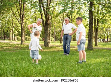 Grandparents with his little cute grandchildren are having fun and playing football on green grassy lawn. Happy family playing soccer on summer meadow. Active family play soccer in their leisure time