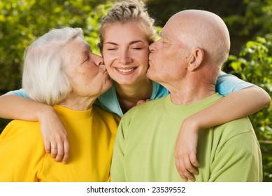 Grandparents kissing their granddaughter