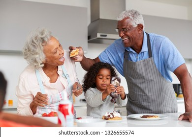 Grandparents In Kitchen With Granddaughter Making Pancakes Together
