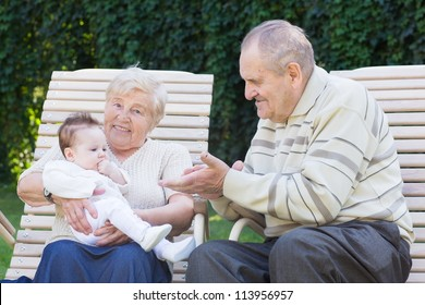 Grandparents playing with a little baby girl outside in the garden