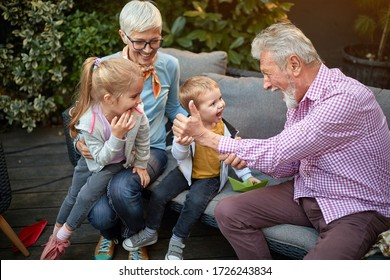 grandparents playing with their grandchildren on a sofa in the backyard