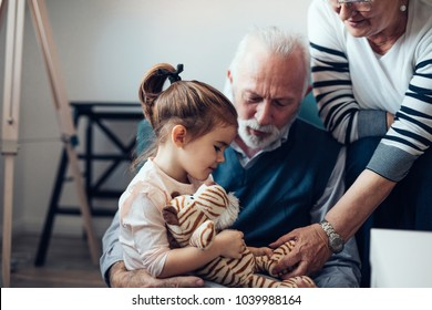 Grandparents playing with their granddaughter