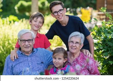 e9e5bd5cb2f Grandparents pose for the photo with their grandchildren in the garden in  summer