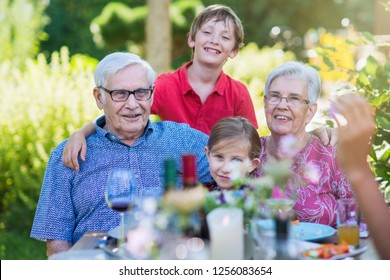 Grandparents pose for the photo with their grandchildren in the garden in summer