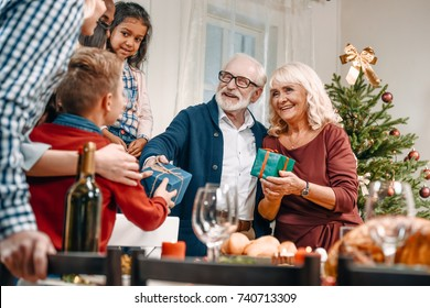 grandparents presenting christmas gifts to kids in beautiful decorated apartments