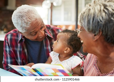 Grandparents Reading Book With Baby Granddaughter At Home