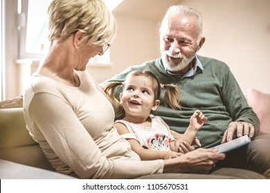 Grandparents reading a book with granddaughter.