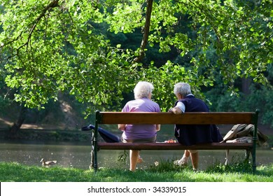 Grandparents are sitting on the bench and talking to each other in the spring park