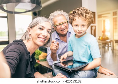 Grandparents taking care of their 6 years old grandchild - Grandmothers taking a selfie with her family at home
