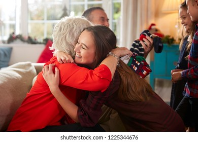 Grandparents Thanking Grandchildren For Gifts As They Celebrate Christmas Day At Home Together