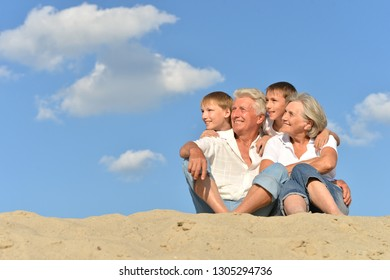 Grandparents with their grandchildren on the sand