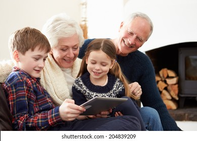 Grandparents Using Digital Tablet On Sofa With Grandchildren