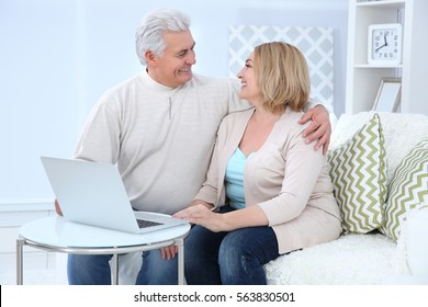 Grandparents using laptop at home