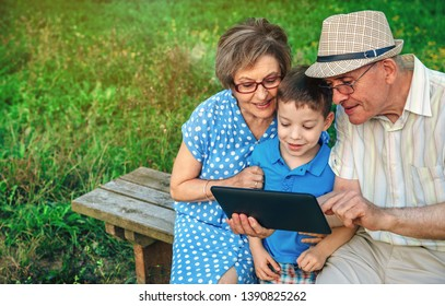 Grandparents using the tablet with their grandson sitting on a bench outdoors