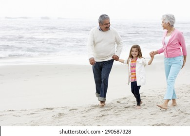 Grandparents Walking Along Beach With Granddaughter