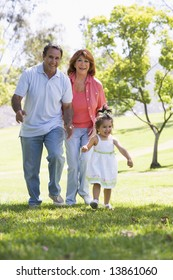 Grandparents walking in park with granddaughter