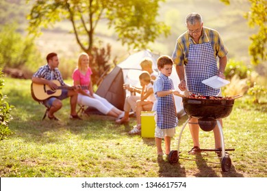 grandson cooking on campfire with grandfather on camping