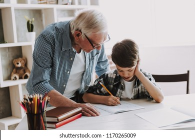 Grandson Doing School Homework with Old Man Home. Family Relationship Between Grandfather and Grandson. Grandpa Teaching, Male Grandchild, Learning Concept. Relations and People Concept.