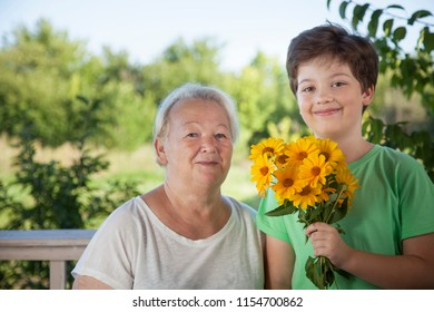 grandson gives grandmother flowers, a child with a gift for an elderly woman in a summer garden.
