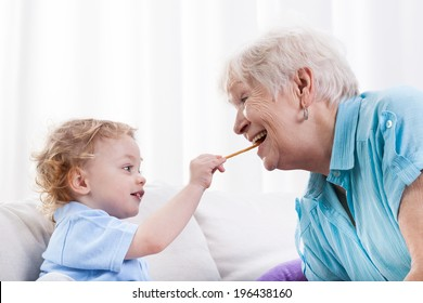 Grandson and his grandma eating together, horizontal