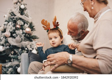 Grandson in hug of his grandparents, wearing Rudolph's antlers , enjoy in their attention making old ones happy and proud of him.