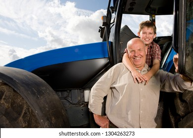 Grandson hugging grandfather farmer by tractor at camera