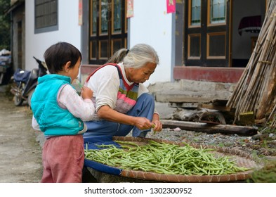 Grandson with lolipop and Grandmother trimming beans in Shangshe village on Fengle lake Huangshan, Anhui, People's Republic of China - October 14, 2011