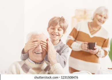 Grandson playing hide and seek with his grandfather, smiling grandmother behind them