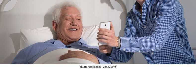 Grandson showing his sick grandfather new mobile phone
