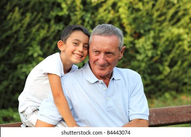 grandson smiling with grandfather in a park