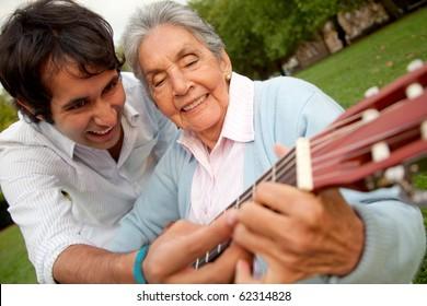 Grandson teaching her grandma how to play the guitar