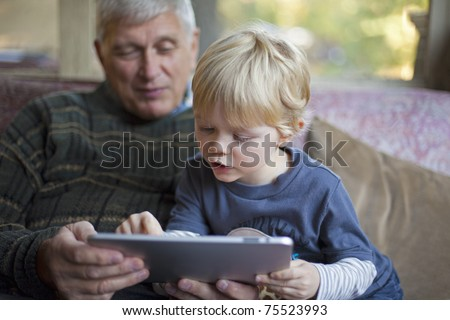 Grandson using touchscreen tablet PC with grandfather
