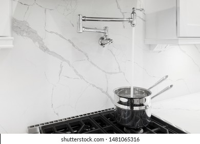 Granite backsplash with pot filler faucet, chrome pot on stove filling with water, white kitchen cabinets
