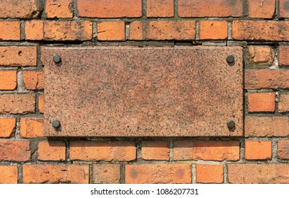 Granite board with metal pins on an old brick wall