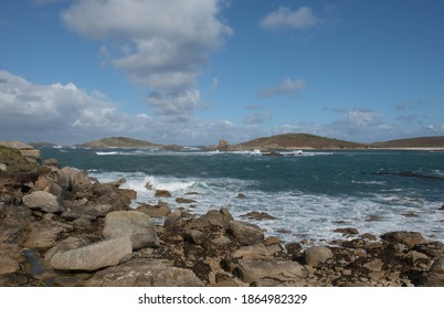Granite Boulders on the Coast with a Cloudy Blue Sky, Rough Seas and the Island of Samson in the Background from Bryher in the Isles of Scilly, England, UK