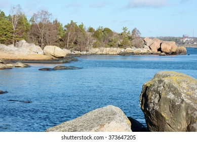 Granite boulders, rocks and some trees in the Swedish shoreline of the Baltic sea. This is outside Karlshamn in February.