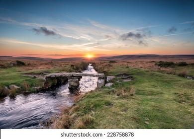 A granite clapper bridge at sunset on Dartmoor