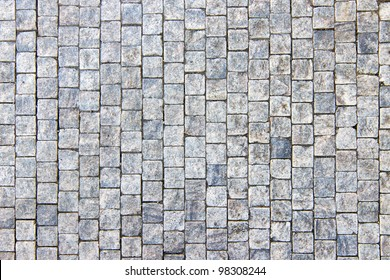 Granite cobblestoned pavement background. Full frame of regular square cobbles in rows. Natural stone textured background