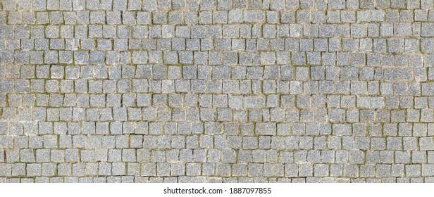 Granite cobblestoned pavement background. Stone pavement texture. Abstract background of cobblestone pavement close-up. Seamless texture.