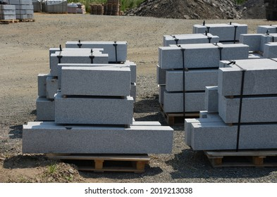 granite curbs of cut granite. smooth stoneware products stacked on a pallet ready for transport to the construction site. curbs vary in length