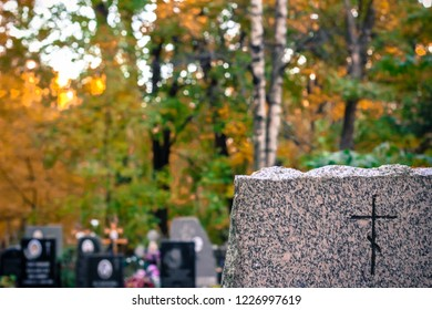 granite gravestone with an engraved traditional Orthodox cross. Autumn Orthodox Cemetery