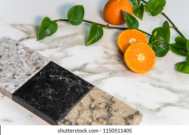 Granite, marble and quartz square color samples of kitchen countertop over white carrara marble natural stone slab and fresh oranges on it