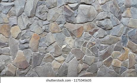 Granite. Granite masonry. Rock. Stone wall. Natural stone. Background of granite stones. Vintage background. Decorative wall granite