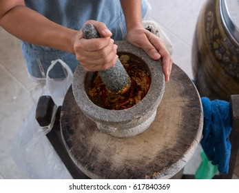 Granite mortar and pestle with spices ready for grinding. woman is grinding chili and garlic by Granite mortar and pestle.